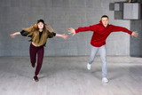 Guy and girl in dance movement. Modern style young dancers performing hip-hop dance on studio background. Teenagers skill and talent of modern dance.