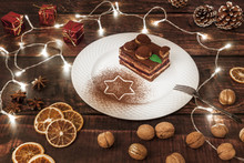 Wooden Table With Lights, White Plate With Christmas Cake, Walnuts, Dried Orange, Anise And Red Gifts