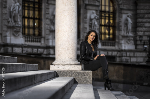 Lifestyle portrait of a woman wearing black jeans and leather jacket Poster