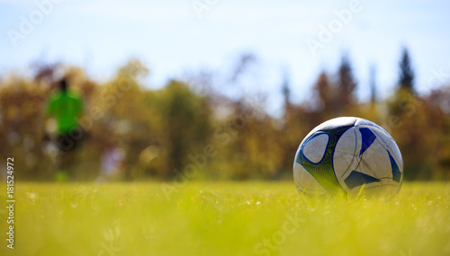 Zdjęcie XXL Piłka w polu po prawej stronie gotowy do kopnięcia. Niewyraźne graczy i tło przyrody.