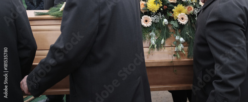 Fototapeta Sargträger tragen einen mit Blumen geschmückten Sarg