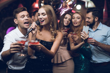A Woman In A Black Dress Is Singing Songs With Her Friends At A Karaoke Club. Her Friends Do Selfie.