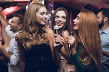 Three Beautiful Girls Sing In A Karaoke Club. Behind Them Are Men Waiting For Their Turn.