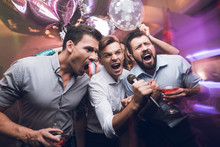Three Men Sing At A Karaoke Club. Young People Have Fun In A Nightclub. They Are Very Cheerful And They Smile.