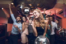 Young People Have Fun In A Nightclub And Sing In Karaoke. In The Foreground There Is A Woman In A Black Dress.