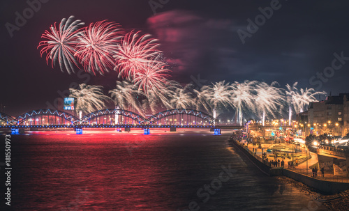 Colorful fireworks in Riga city with panoramic view over the river Daugava and railroad bridge. New year celebration.