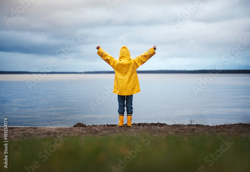 Photo  Little Boy in Yellow Rain Coat raising his arms in front of an autumn Lake: He h
