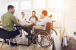 Leinwanddruck Bild - A man in a wheelchair communicates cheerfully with employees of the office during a business meeting.