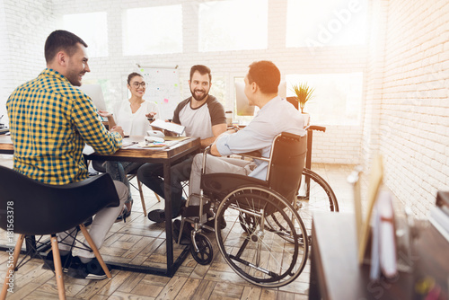 Photo  A man in a wheelchair communicates cheerfully with employees of the office during a business meeting