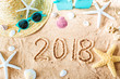2018 text in the sand with beach accessories