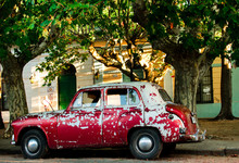 Old, Rusty And Red Car Parked In A Street Under The Trees