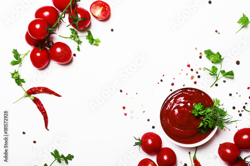 Cuadros en Lienzo  Tomato ketchup sauce with spices and herbs with cherry tomatoes in a bowl on whi