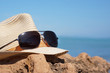 A hat from the sun and sunglasses lie on a stone near the blue sea