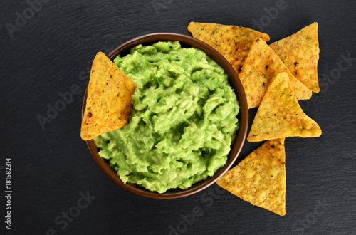 Bowl with guacamole and nachos on the background of a slate board.