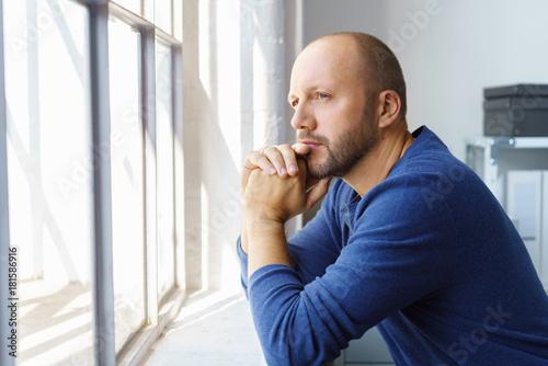 Fotografía  geschäftsmann steht im büro und schaut nachdenklich aus dem fenster