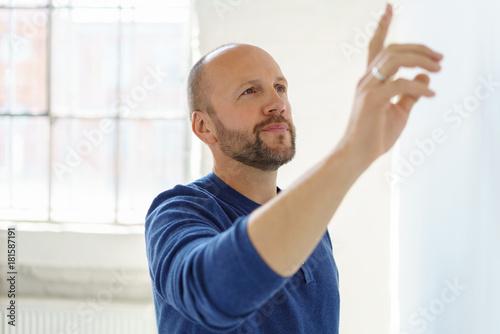 Fototapeta mann steht in der wohnung und zeigt mit der hand auf etwas