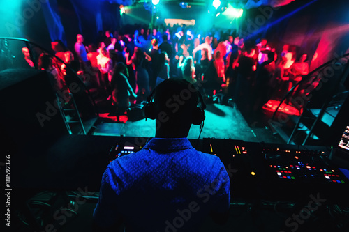 Foto  silhouette of DJ playing music on mixer and a lot of people dancing in nightclub