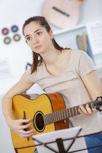 Young Woman Holding Guitar And...
