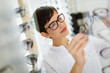 canvas print picture - Pretty young woman is choosing new glasses at optics store