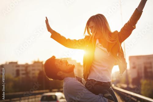 Fotografia Couple in love having fun carrying piggyback - freedom concept