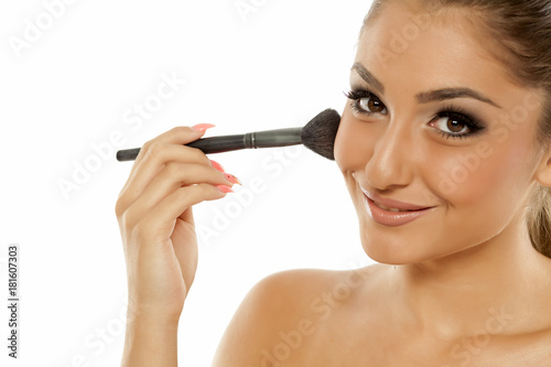 Valokuva young beautiful woman applied blush with a brush