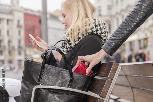 Photo taschendieb klaut geldbörse einer telefonierenden frau