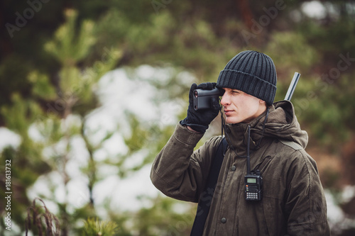 male hunter ready to hunt, holding gun and walking in forest.