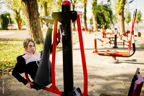 Obraz Young girl has the training and doing exercise outdoors on street simulators. Sport, fitness, street workout concept. - fototapety do salonu