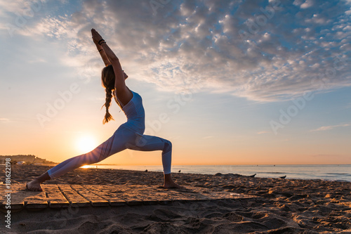 Staande foto School de yoga girl doing sport on the beach
