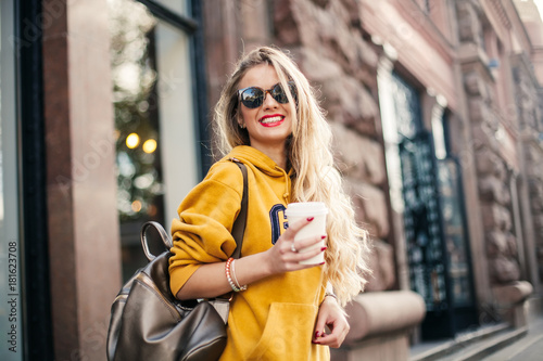 young beautiful blonde drinking coffee walking around the city фототапет