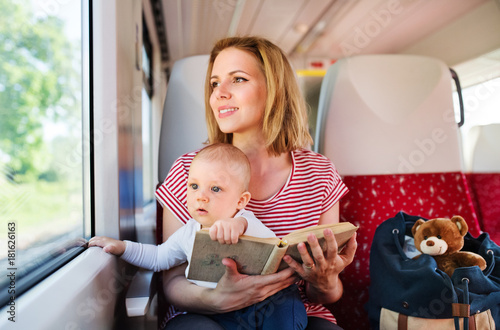 Young mother travelling with baby by train.