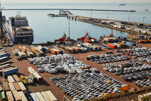 Photo Stands Port Port terminal with a lot of new cars and containers. Business logistic, Water transport