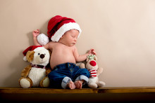 Newborn Baby Boy Wearing A Christmas Hat And Jeans, Sleeping On A Shelf Next To Teddy Bears
