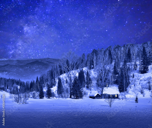 Small wooden house in a night winter mountain landscape with a beautiful starry sky