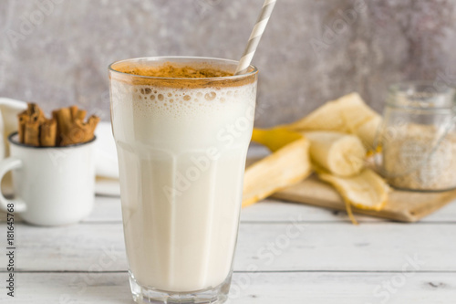 Banana oat protein shake with cinnamon and paper straw in a glass.