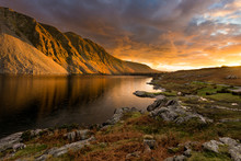 Golden Evening Light Illuminating Mountain At Wastwater In The English Lake District With Moody Dramatic Clouds.