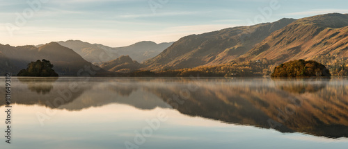Photo Stands Lake Calm reflections in a still Derwentwater on an Autumnal morning in the Lake District.