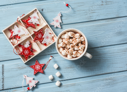 Spoed Foto op Canvas Chocolade Hot chocolate with marshmallows and cinnamon, christmas decorations on a blue wooden background. Christmas background. Free space, top view, flat lay