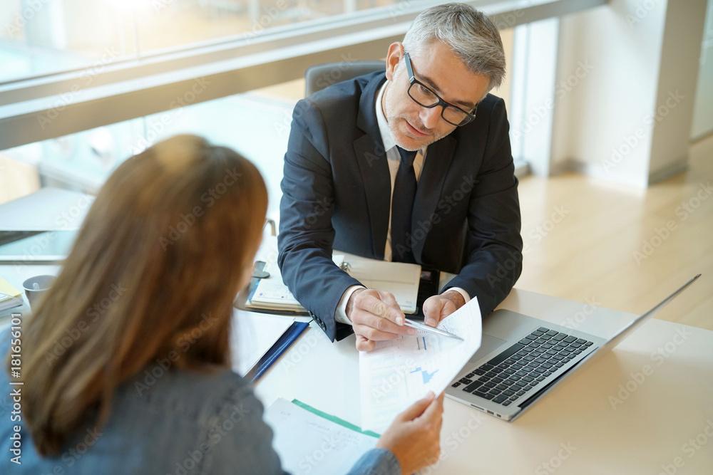 Fototapeta Woman in banker's office signing financial loan for project
