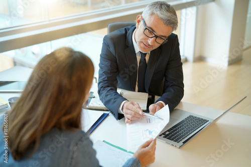 фотографія Woman in banker's office signing financial loan for project