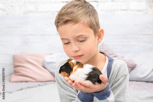 Fotografía  Cute boy with funny guinea pig, indoors