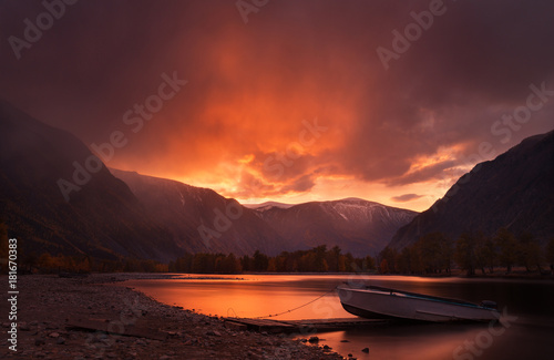 Sunset In The Mountains. Enchanting Autumn Mountain Landscape In Red Tones With Sunset Sky, River with Reflection And Lonely Boat. Mountain Valley With River And Boat On The Sunset Background. Altai