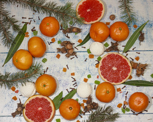 festive background of juicy mandarin with candied fruits and branches of a Christmas tree