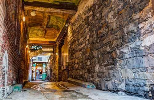 Poster Smal steegje Old town street narrow dark brick alleyway or alley with path