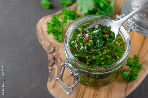 Traditional argentinian chimichurri sauce made of parsley, cilantro, garlic and chili pepper in a glass jar, focus on a spoon with sauce. Selective focus, horizontal image