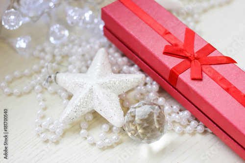 Fototapeta  Red gift box, glittery white star, crystal ball and perly white beads on a white