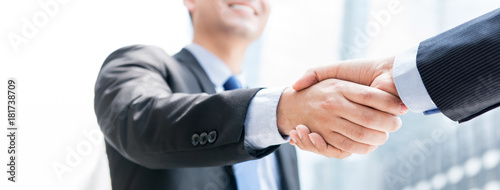 Smiling businessman making handshake with his partner outdoors in the city Wallpaper Mural