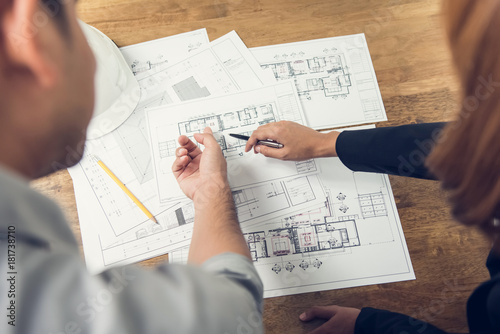 Engineer and architect discussing about blueprint layout design of  electricity plan