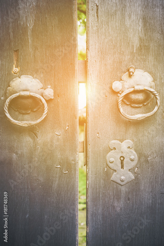 Photo Two old iron ring handles on a door standing ajar