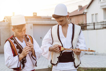 Teen Boys In Traditional Albanian Costume Playing Music With Flute And String Instrument In The Evening Sunlight